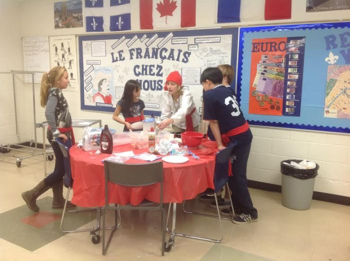 Teacher with students, preparing crepes for French Canadian Heritage Day.